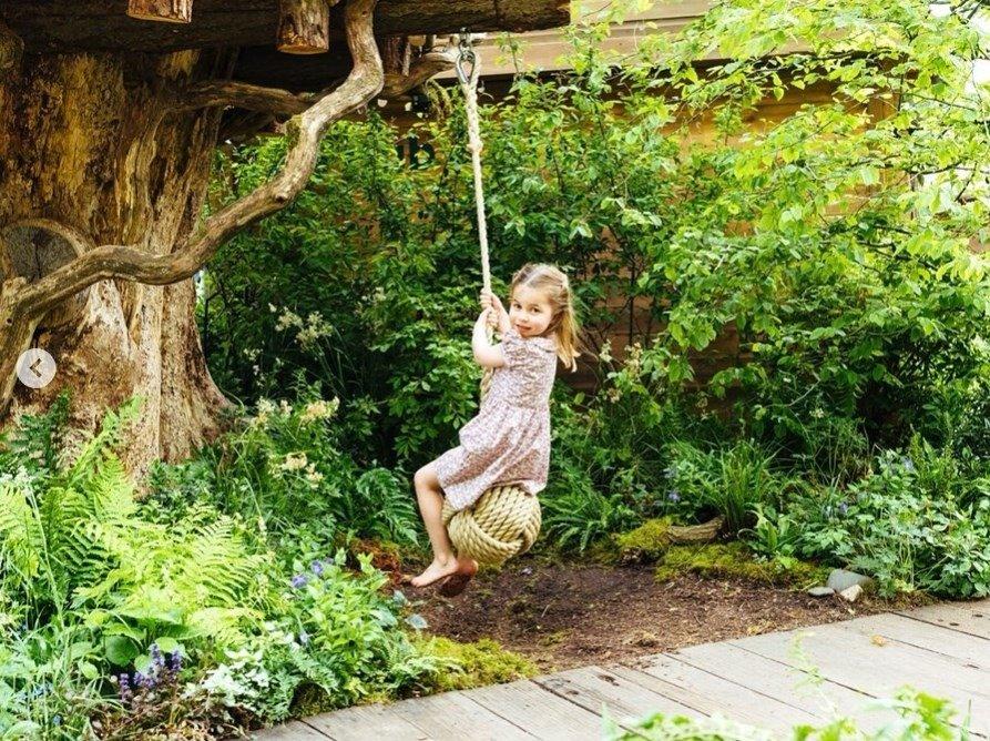 La princesa Charlotte jugando con la hamaca del jardín.